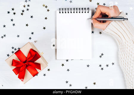 Holiday decorations and notebook with wish list on white rustic table, flat lay style. Planning concept. - Stock Photo