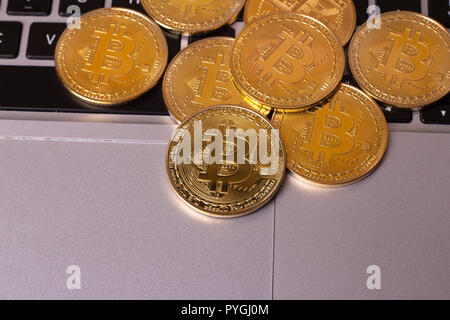 A stack of golden bitcoin coin on a silver keyboard of laptop. Virtual cryptocurrency concept. Mining of bitcoins online bussiness. Bitcoins trading.  - Stock Photo