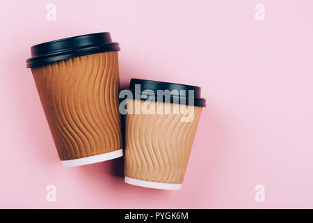 Two brown craft cups of coffee to go on pastel pink background. Flat lay style. Place for text. - Stock Photo