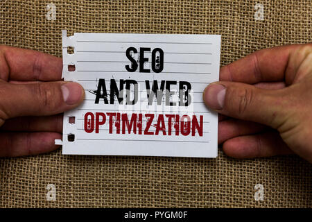 Text sign showing Seo And Web Optimization. Conceptual photo Search Engine Keywording Marketing Strategies Man holding piece notebook paper jute backg - Stock Photo