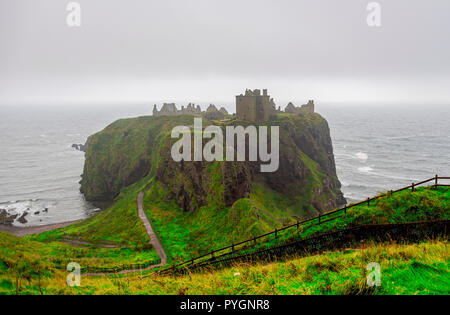 A view of famous tourist attraction Dunnotar Castle in poor Scottish autumn foggy weather, Aberdeenshire, Scotland - Stock Photo