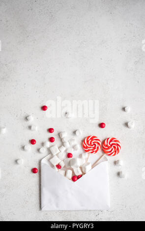 Christmas composition with sweets and envelop, flat lay on white, copy space. Christmas greeting card with candies. - Stock Photo