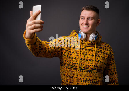 Man wearing hoodie and headphones while taking selfie with phone - Stock Photo