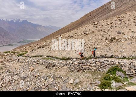 Trekkers hiking the beautiful Engels Peak Meadows trek alongside a traditional Pamiri dyke, or water canal, Langar, Tajik Wakhan, Pamir Mountains, Taj - Stock Photo