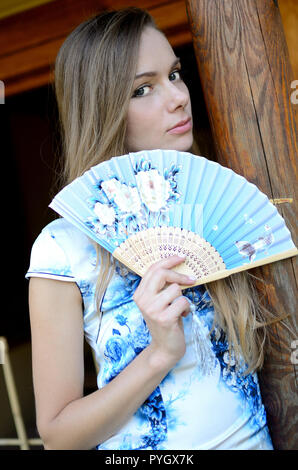 Female model from Poland wearing traditional Chinese dress, holding fan. Woman posing in Asian style park. - Stock Photo