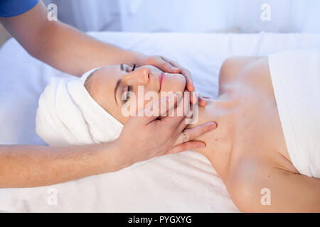 woman doing massage of the face and neck treatments - Stock Photo