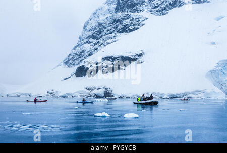 Snowfall over the motor boat with tourists and kayaks in the bay with rock and glacier in the background, near Almirante Brown, Antarctic peninsula - Stock Photo