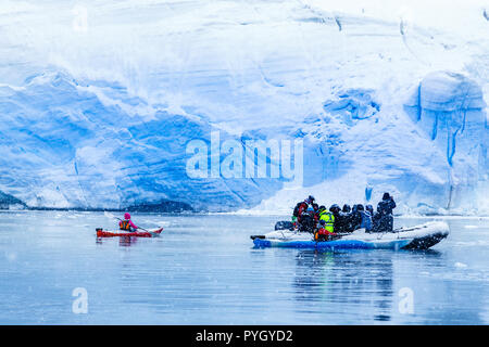 Snowfall over the motor boat with tourists and  kayaks in the lagoon with huge blue glacier wall in the background, near Almirante Brown, Antarctic pe - Stock Photo
