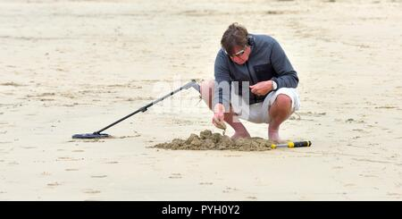 A man using a metal detector on a uk beach - Stock Photo