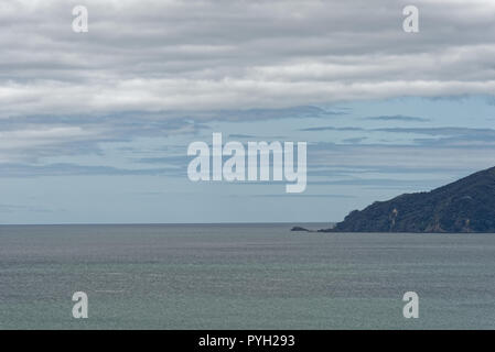 Land ocean and the sky meet at the horizon on an overcast day - Stock Photo