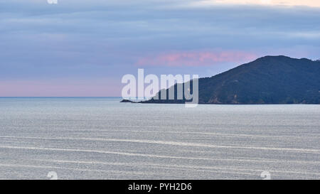 Land ocean and colorful sky meet at the horizon at sunset - Stock Photo