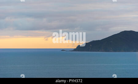 Land ocean and the sky meet at the horizon at sunrise - Stock Photo