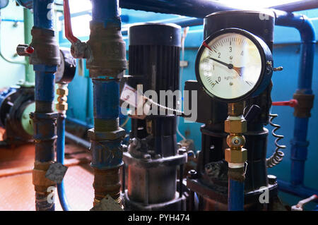 A pressure gauge on the pipeline showing the water pressure after the electric pumps. - Stock Photo