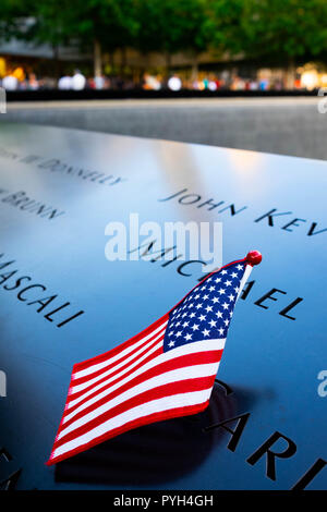 The names of some of the victims marked by the American flag on the 9/11 World Trade Centre Memorial fountains in Lower Manhattan, New York City - Stock Photo