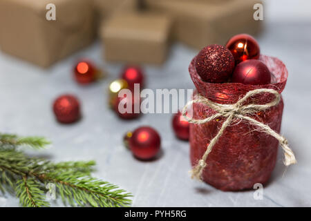Red ornaments, branches and gifts on the blurred background, Christmas and New Year holiday concept - Stock Photo
