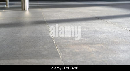 on the floor the sun's rays. The Shine of sunlight on pressed Sandstone paving slabs is an unusual perspective of photo paving slabs with a small depth of field in perspective. - Stock Photo