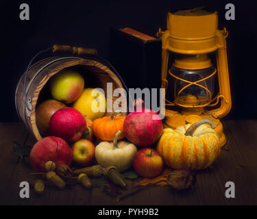 Abstract still life displaying fresh and dry harvest symbols and a yellow gas lantern, against wooden background and decorated with colorful fall leav - Stock Photo