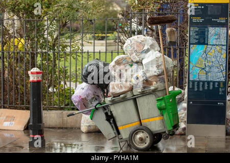 Plastic bags full of autumn leaves and packaging refuse and street waste, collected from the area around the Tower of London, UK. - Stock Photo
