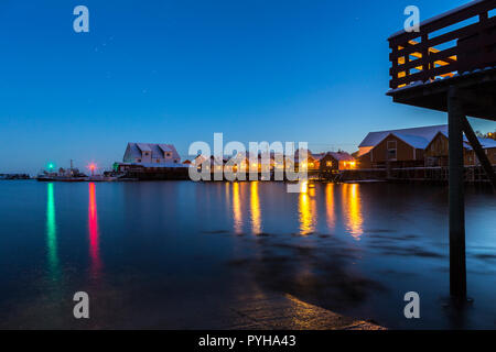Houses at the waterfront in the harbor of Tindshamna illuminated after nightfall on the Lofoten Islands, Norway. - Stock Photo