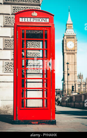 London's iconic telephone booth with the Big Ben clock tower in the background - Stock Photo