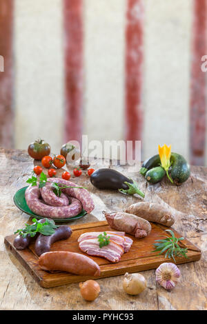 Selection of French Raw sausage with arugula leaves on wooden board with vegetable on the table plate isolated on old timbered wall background. - Stock Photo