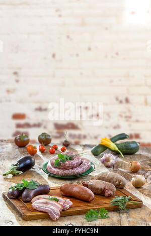 Selection of French Raw sausage with arugula leaves in a wooden board,vegetable on the table on old white cracked red brick wall background. - Stock Photo