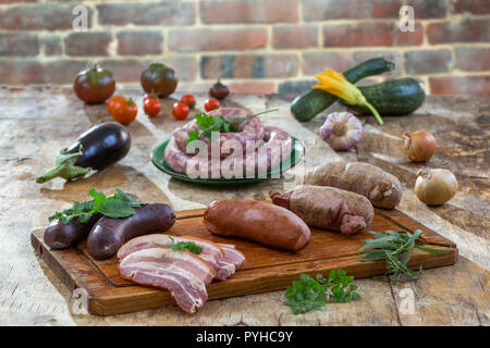 Selection of French Raw sausage with arugula leaves in a wooden board,vegetable on the table on old red brick background. - Stock Photo