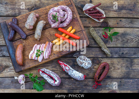 Selection of French Raw charcuterie board, with arugula leaves and dry sausage over a wooden background - Stock Photo