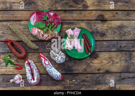 Selection of French Raw charcuterie in green plates, with arugula leaves and dry sausage over a wooden background - Stock Photo