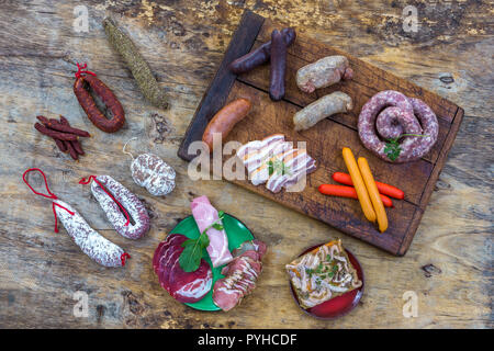 Selection of French Raw charcuterie board, with arugula leaves and dry sausage over a wooden backgroundi - Stock Photo