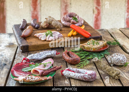 Selection of French Raw charcuterie board, with arugula leaves and dry sausage over old red timbered wall background. - Stock Photo