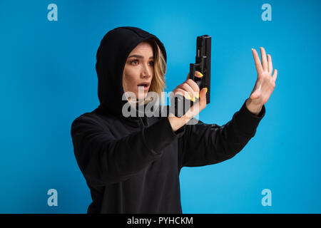 Hooded young girl presenting gun while surrendering. Airsoft game loser - Stock Photo