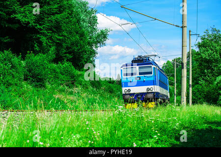 A blue electric locomotive passing the Czech countryside. A train running through the green valley. Rail transport in the Czech Republic - Stock Photo