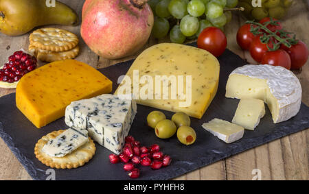 Cheese board with three cheeses, gouda with pimento, gouda with cumin seeds and roquefort blue cheese  and camembert close up on rustic wooden backgro - Stock Photo