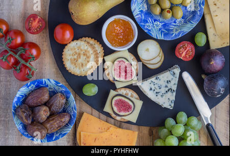 Cheese board with three cheeses, gouda with pimento, gouda with cumin seeds and roquefort blue cheese  and assorted fruits close up on rustic wooden b - Stock Photo