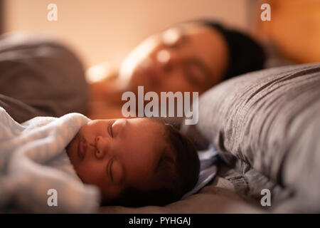 A baby asleep on bed with his mum in the background. - Stock Photo