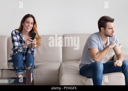 Woman communicates by phone behind man back - Stock Photo