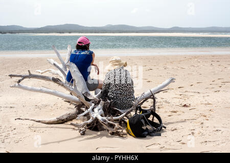 Rear view of two females with hats on sitting on a piece of driftwood within a beautiful sandy landscape. - Stock Photo