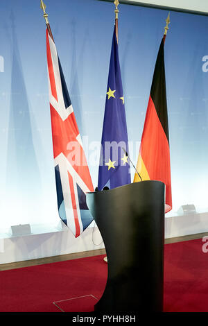 Berlin, Germany - The flags of Great Britain, the European Union and Germany hang on standards behind two standing desks in front of a logo wall in a press room of the Foreign Ministry. - Stock Photo