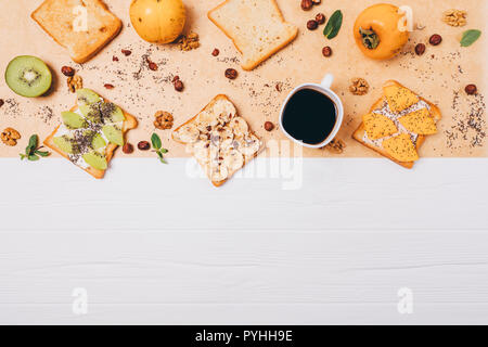 Food composition healthy sandwiches with persimmon, kiwi, banana, chia and nuts for breakfast on white wooden table, top view. Flat lay frame sweet to - Stock Photo