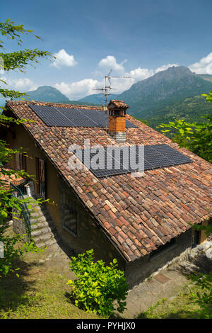 Solar panels and chimney pot on the roof of an old Italian cottage (portrait). - Stock Photo