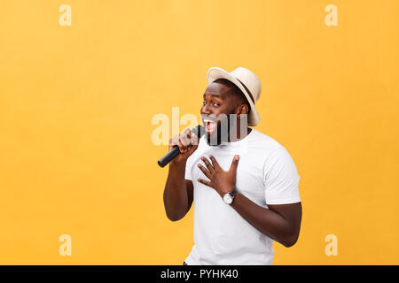 young handsome african american boy singing emotional with microphone isolated on yellow background, in motion gesturing - Stock Photo