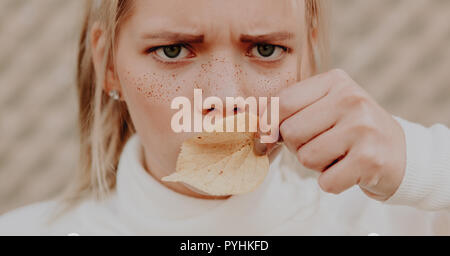 Young woman with freckles on her face frowning and covering the mouth with a leaf - Stock Photo