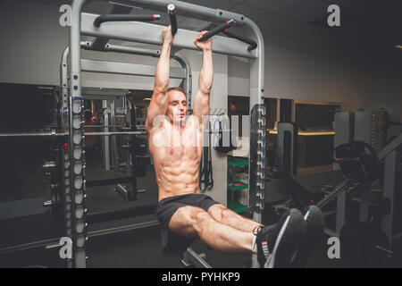 Fit young man doing leg raises on a pull up bar - Stock Photo