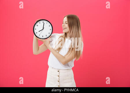Portrait of an excited young girl dressed in white t-shirt pointing at alarm clock and looking at camera isolated over pink background - Stock Photo