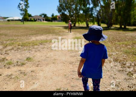 A mother walking with her children through an urban parkland, Ross river area, Townsville, QLD, Australia - Stock Photo