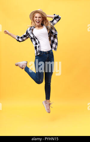 Portrait of surprised young woman in black pants jumping in front of yellow wall. Indoor portrait of young lady in fooling around in studio - Stock Photo