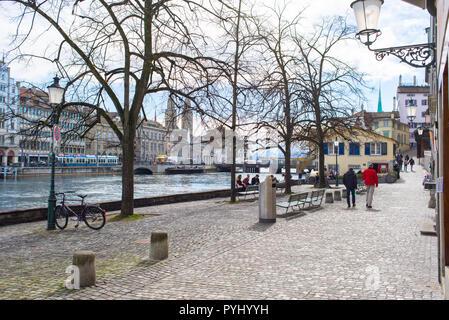 Zurich, Switzerland - March 2017: People walking on Schipfe, a riverside street along river Limmat in Zurich city centre, Switzerland - Stock Photo