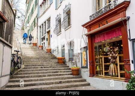 Zurich, Switzerland - March 2017: Couple walking in small medieval alley street in Zurich city centre, Switzerland - Stock Photo
