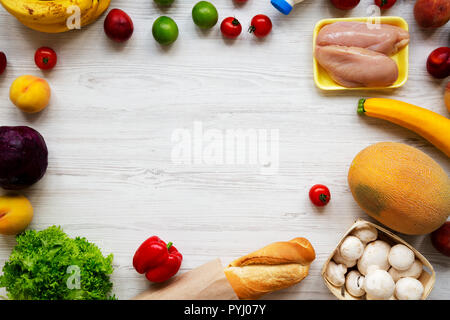 Frame of various healthy food on white wooden background. Fresh fruits, vegetables, greens, meat, milk. Top view, overhead, from above. Shopping groce - Stock Photo